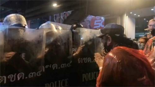 16日夜、機動隊に手を合わせて抗議する女性