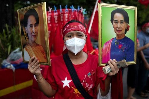 ヤンゴンでスー・チー氏の肖像を掲げる国民民主連盟(NLD)の支持者(写真:ロイター/アフロ)