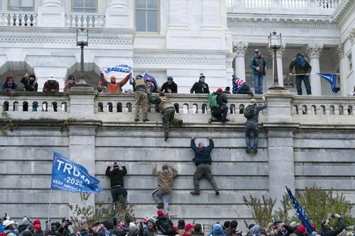 6日に起きた暴動で、議事堂の壁によじ登るトランプ氏支持者たち(写真:AP/アフロ)