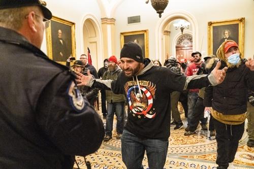 上院議場前で中に突入しようとするトランプ支持者(写真:AP/アフロ)
