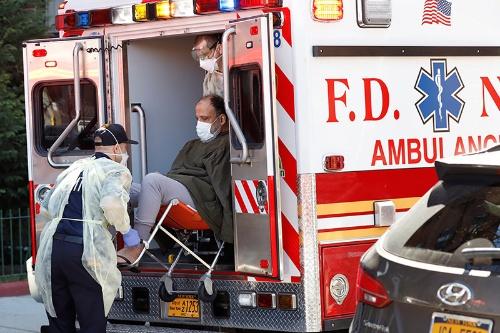 新型コロナウイルス感染症の患者を救急車に運び込むニューヨーク市の消防局員(写真:ロイター/アフロ)