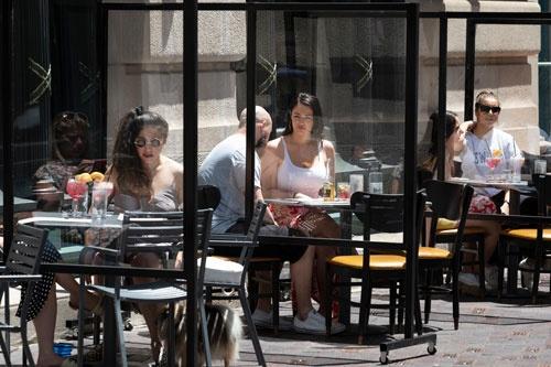 6月12日、ボストンのレストランでは屋外で食事を楽しむ人たちの姿が見られた。テーブルの間にはシールドが設置されている(写真=AP/アフロ)