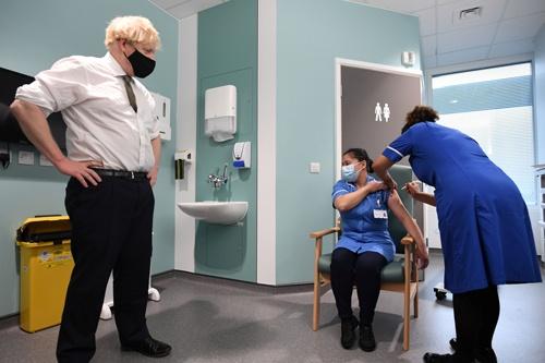1月4日、英国で英アストラゼネカ製の新型コロナワクチンの接種が始まった。左は接種を見守るジョンソン英首相(写真:代表撮影/ロイター/アフロ)