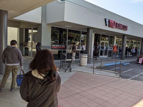 スーパーの外で6フィート以上の間隔を確保して入店を待つ人々の列。写真右奥にスーパーの入り口がある。
