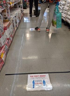 6フィート間隔の目安としてスーパー内のレジ周辺の床に張られた目印