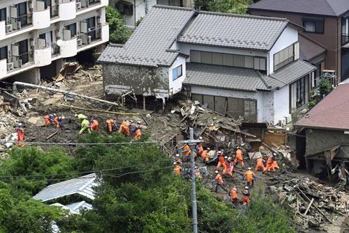 静岡県熱海市の土石流災害現場で捜索活動をする消防隊員ら(写真:共同通信)