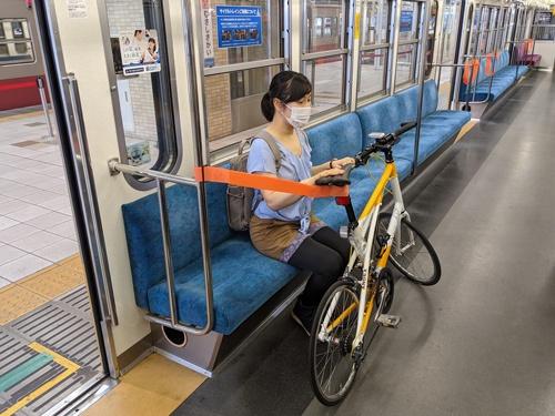手すりに取り付けられたベルトで自転車を固定する
