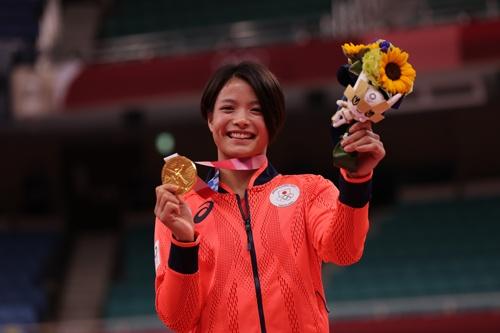 柔道の阿部詩選手が掲げるメダルは小型家電の金属をリサイクルし、公式ウエアは再生ポリエステルで製作された(写真:代表撮影/日本雑誌協会)
