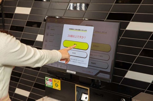 酒類を購入する場合、レジの画面に年齢確認のメッセージが表示される。同時にバックヤードのスタッフがカメラを通して購入者の顔を目視する