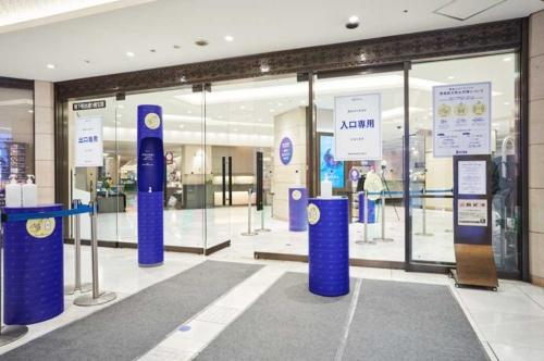 2020年5月30日の営業再開後、入り口を3つに制限した伊勢丹新宿店。既存の入り口のデザインと合わせるため、新たに消毒液を置く専用の台などに統一感を持たせた。ブルーは伊勢丹のロゴの色だ