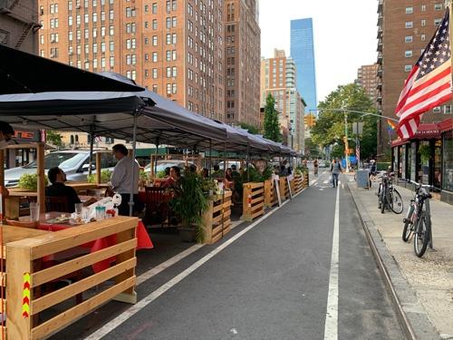 おしゃれに敏感な人が集うマンハッタンのチェルシーと呼ばれる地域で屋外での飲食を楽しむ人々
