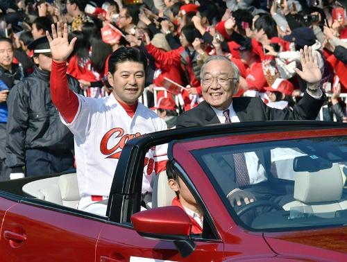 16年、セ・リーグ優勝を祝うパレードでファンに手を振る。右は松田元オーナー(写真:共同通信)
