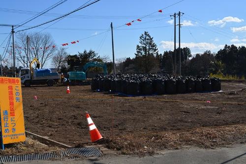 一部の地域では、土の表面を削り取って黒い袋に詰め込む除染作業が続く