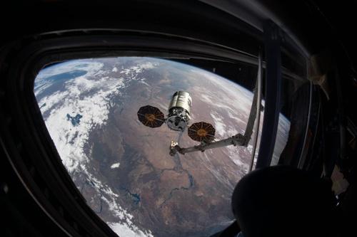 ISSのロボットアームが積み荷をつかもうとする瞬間の写真(NASA提供)