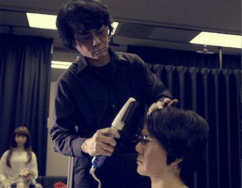 自分に似せたロボットの頭髪を整える石黒浩教授。自分に酷似させることで人間の本質を探っている(写真:大阪大学)