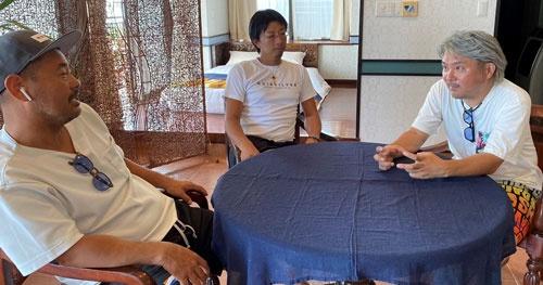 ホテルの部屋でオーナーと相談する酒匂さん(右)と平良さん(左)