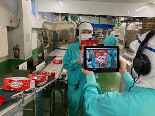 「フルグラ」を手に持ち、製造工程を実況中継するカルビー清原工場のスタッフ