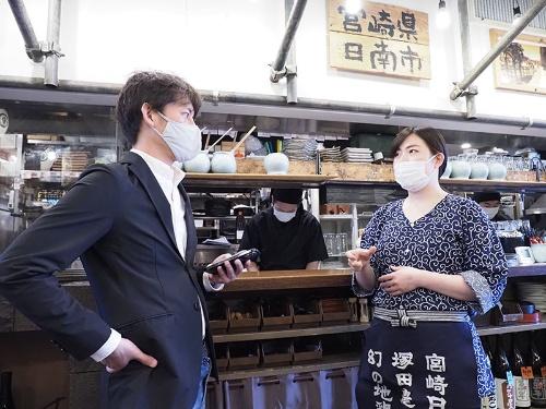 塚田農場秋葉原中央通り店の木曽巴絵店長(右)と話す野本COO。休業や営業時間の短縮が続く中、各店舗は奮闘している