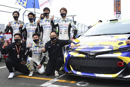 水素エンジンを搭載したレースカーと記念撮影するトヨタ自動車の豊田章男社長(前列右、写真:共同通信)