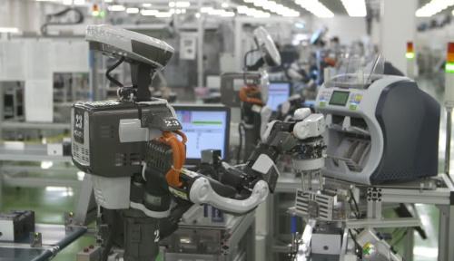 ロボットが釣銭機を組み立てる(グローリーの埼玉工場)