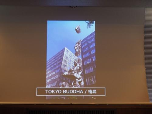 椿昇氏の作品「TOKYO BUDDHA」は、ビルの谷間にブッダが次々と落下し、最後には溶けて金塊になるという表現を、AR技術と「PLATEAU」のデータを使って実現している。写真は2021年6月29日の「東京ビエンナーレ2020/2021」に出展するARアートの共同開発に関する記者説明会より(筆者撮影)