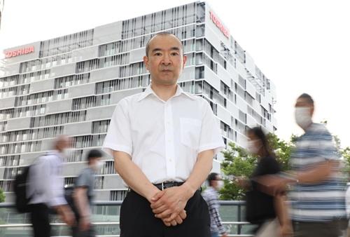 東芝エネルギーシステムズ本社(川崎市)の前に立つ小里正義氏。労働組合には頼らず、会社を相手に裁判で争っている(写真:都築雅人)