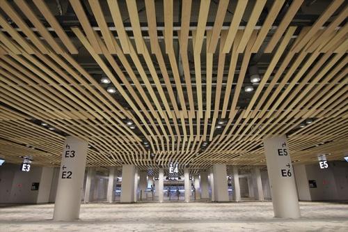 天井の木ルーバーが波打つようにスタンドへと導く(写真:宮沢 洋)