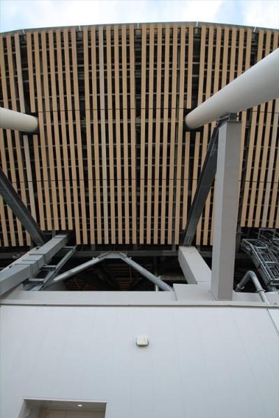 最上部の庇を見上げる。この庇のルーバーは、高い位置にあってメンテナンスが難しいため、本物の木材ではなく、木に見えるプリントを使っている(写真:宮沢 洋)