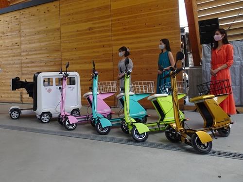 カラフルなデザインの3輪電動バイク「GOGO!」と、三菱電機の「移動式ゴミ箱」(左)