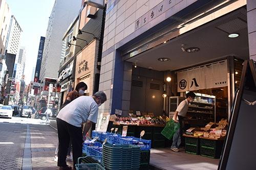 オフィスや飲食店が立ち並ぶ旬八青果店の赤坂店。店先にはモモやスイカなどが並び、利用客が品定めしていた