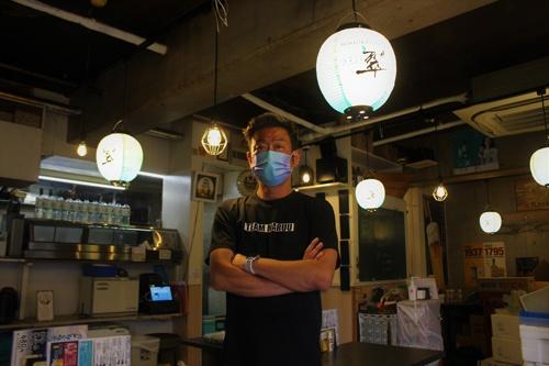JR横浜駅近くに立つ、まるう商店の杉原昌和氏。新商品のジャパニーズジン「翠」の普及に全面協力する