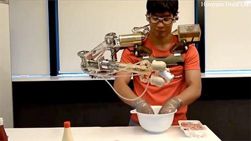 早稲田大学の岩田浩康研究室で開発した「3本目の腕」は顔の向きと音声による指示で作業を手伝ってくれる