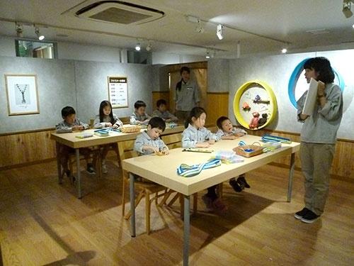YKKは東京・秋葉原にあるイベント施設「ものづくり館 by YKK」で、ファスナーを使った手芸などを学べる機会を提供。大人だけでなく、子ども向けのイベントもある(写真上)。今年10月には、キッザニア東京でファスナーの構造を伝えて、実際にポーチを作る「ファスナーウイーク」に協賛した