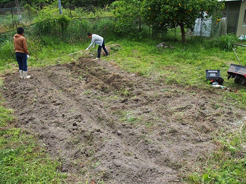 畑を耕す共生舎の住人。(写真提供:石井新/共生舎)