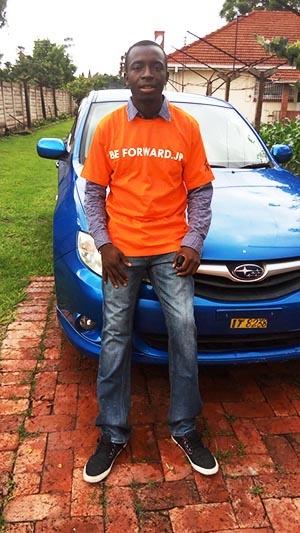 「ビィ・フォアード」のTシャツ(販促グッズ)を着たジンバブエの青年。社名入りのシャツを好んで着てもらえるように、現地の人が好む色やデザインを採用している。