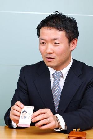 NEC経営企画本部主任の土屋俊博氏、38歳。NECの名刺とはほかに、中小企業診断士として活動するためイラスト付きの名刺も持ち歩く。東大卒(写真は北山 宏一)