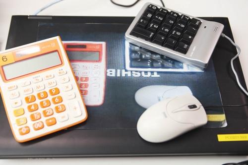 ノートパソコンに電卓とテンキー、マウスをセットにして置くのがルール。原寸大のカラーコピーで置き場所を示せば、誰でもピタリと戻す(写真:鈴木愛子)