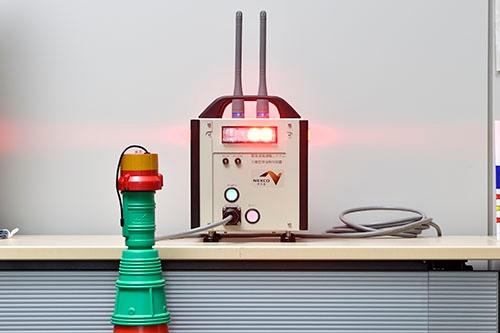自社製品例②。高速道路上の作業員を守る警報機。作業エリアを指定した路上のコーンに触れたクルマなどがあると、作業エリア全体に瞬時に大音響の警報を鳴らす装置。NEXCO中日本の困り事を聞いて製品化した