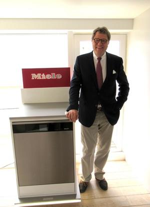 17年6月に日本を訪れたツィンカン社長。右は最新の食器洗浄機エコ・フレックス。洗浄から乾燥まで僅か58分(標準運転時間)で終えられる。「世界中の忙しい女性向け」だ