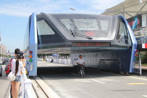 車両をまたいで走る大型の「空中バス」。河北省での試験走行は期待を集めたが…(写真:Imaginechina/アフロ)