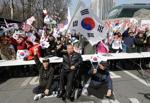 朴氏の支持者が集まり、弾劾決定に抗議。座り込みをする人も(写真:AP/アフロ)