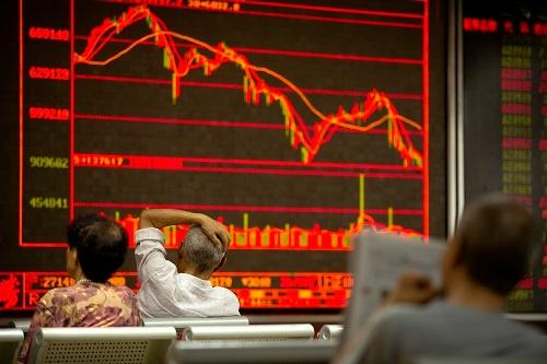 米中貿易戦争が勃発した7月6日、株価を見つめる中国・北京の投資家たち(写真:AP/アフロ)