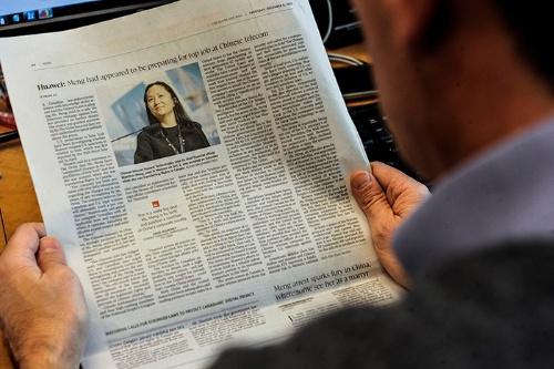 カナダ・モントリオールで12月6日、華為技術の孟晩舟逮捕を伝える新聞を手にするジャーナリスト(写真:AFP/アフロ)