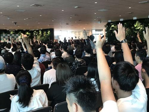 手をまっすぐ伸ばす参加者たち。「はい、はい」という声が響き渡った。写真中央にうつる参加者は、立ち上がり手を伸ばしていた