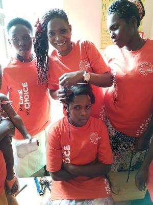 お互いに髪を結び合う職業訓練(ウガンダにて筆者撮影)