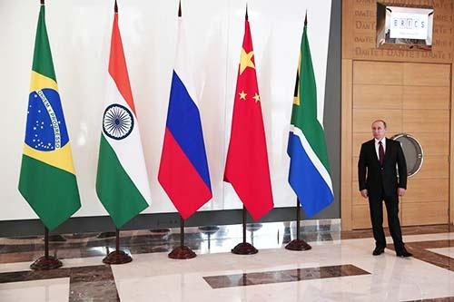 2015年のBRICS首脳会議で、各国の国旗(左から、ブラジル、インド、ロシア、中国、南アフリカ)の横に立つ、ロシアのプーチン大統領。(写真:代表撮影/AP/アフロ)