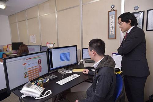 八面六臂では、社内で配送状況を細かく把握できる。松田社長(左)がシステムを操作する様子を見守る斎藤氏(右)(写真:菊池一郎)