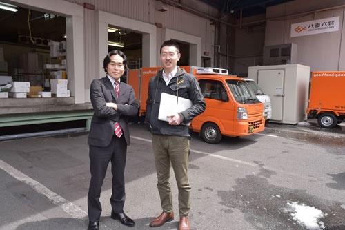 本社オフィスがある物流倉庫前に立つ斎藤事業統括本部長(左)と松田社長(右)(写真:菊池一郎)