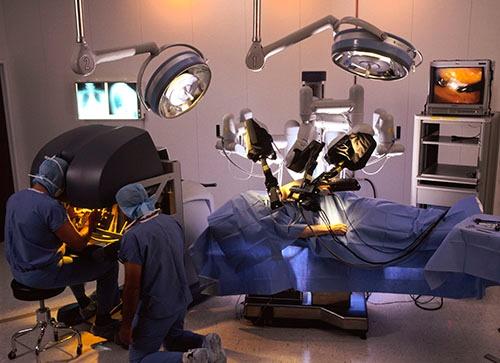 ダヴィンチを使ったロボット手術の様子。患者さんがベッドに寝ていて、「クモの足」状のロボットが上から覆いかぶさり、何本もの触手が出てきてお腹の中に入っていく感じです。左にあるのが、外科医がダヴィンチを操作する「コンソール」で、顔を突っ込んでいる人が手術を執刀している外科医です(写真=SCIENCE PHOTO LIBRARY /amanaimages)