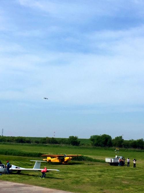 八谷さんを乗せたM-02Jがジェットエンジンの音を響かせて自力で離陸し、高度を上げていく姿に子供たちは口あんぐり。旋回して着陸するまでじっと見守っていました。手持ちの古いスマホで撮るとこんな大きさになってしまいますが、見ている実感には近いかもしれません(Y)。